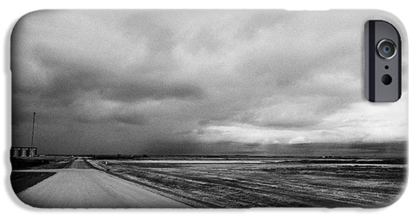 Winter Storm iPhone Cases - storm snow clouds forming over country road on the prairies assiniboia Saskatchewan Canada iPhone Case by Joe Fox