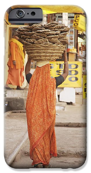 Woman Carrying Cow Dung In Basket On iPhone Case by Paul Miles