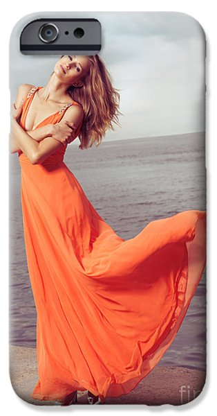 Young woman in orange dress flying in the wind at sea shore iPhone Case by Oleksiy Maksymenko