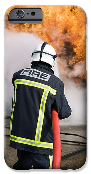Practise iPhone Cases - Firefighter Extinguishing A Fire iPhone Case by Paul Rapson