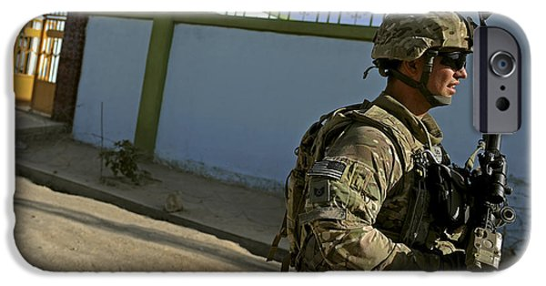 East Village iPhone Cases - A Soldier Patrols The Streets Of Qalat iPhone Case by Stocktrek Images