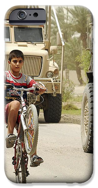An Iraqi Boy Rides His Bike Past A U.s iPhone Case by Stocktrek Images