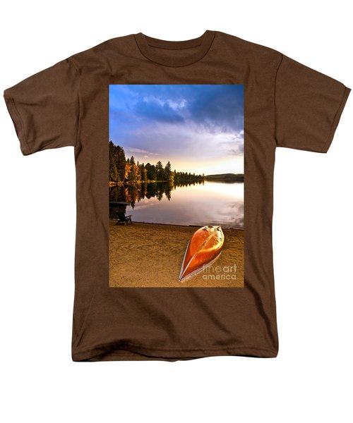 Lake sunset with canoe on beach T-Shirt by Elena Elisseeva