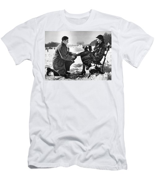 Man Lends A Helping Hand To Put On Skates Men's T-Shirt (Slim Fit) by Underwood Archives