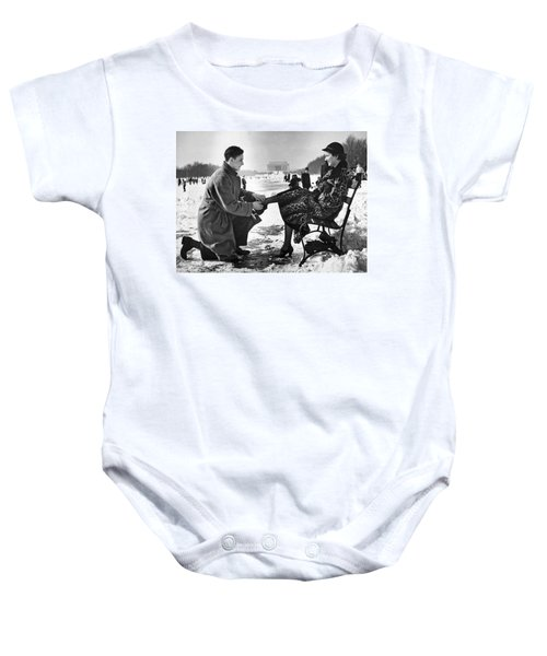 Man Lends A Helping Hand To Put On Skates Baby Onesie by Underwood Archives