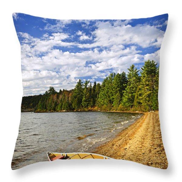 Red Canoe On Lake Shore Throw Pillow by Elena Elisseeva