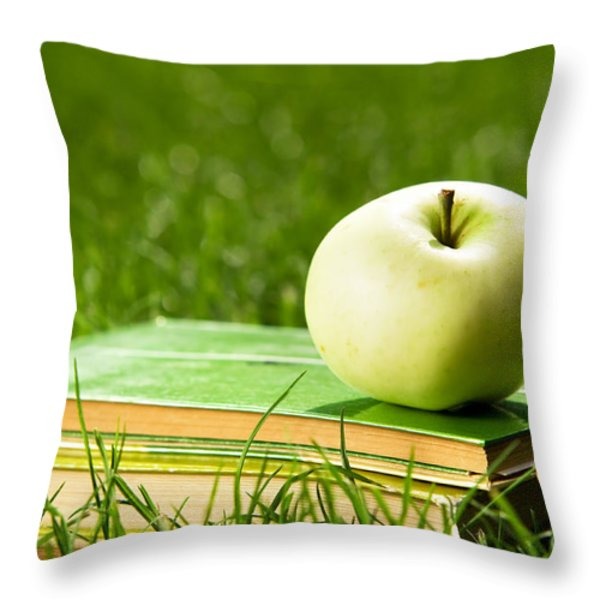 Apple On Pile Of Books On Grass Throw Pillow by Michal Bednarek