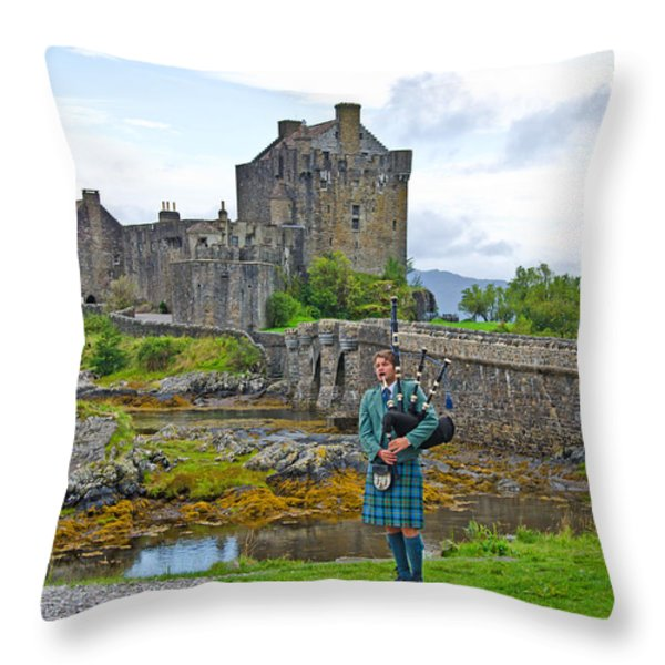 Eilean Donan Castle and the Lone Piper Throw Pillow by Chris Thaxter
