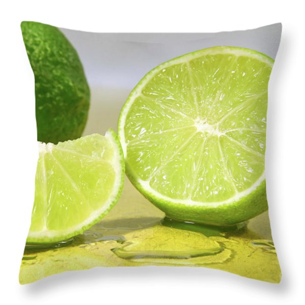 Limes On Yellow Surface Throw Pillow by Sandra Cunningham
