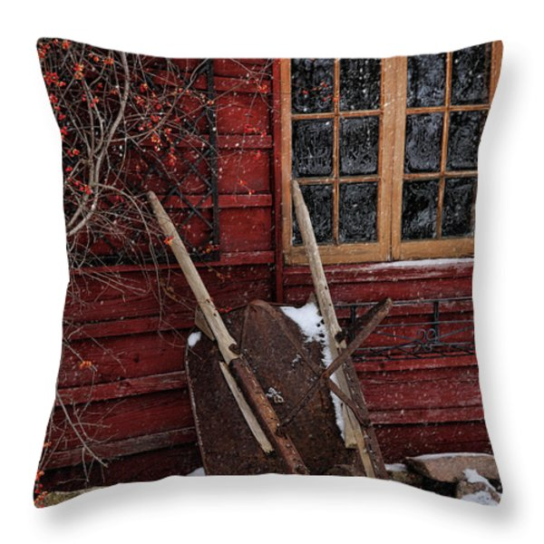Old wheelbarrow leaning against barn in winter Throw Pillow by Sandra Cunningham