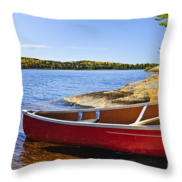 Red Canoe On Shore Throw Pillow by Elena Elisseeva