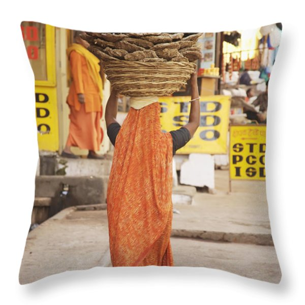 Woman Carrying Cow Dung In Basket On Throw Pillow by Paul Miles