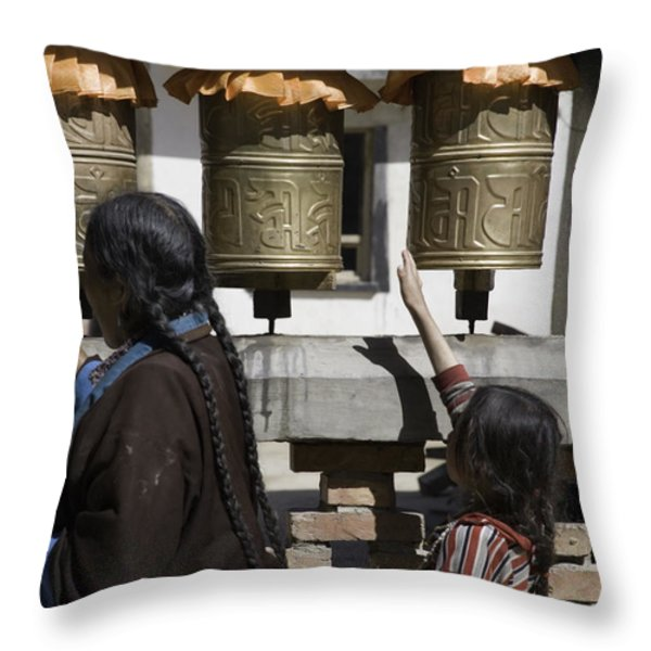 A Buddhist Woman And Child Spin Brass Throw Pillow by David Evans