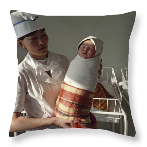 A Nurse Holds A Tightly Wrapped Newborn Throw Pillow by Dean Conger