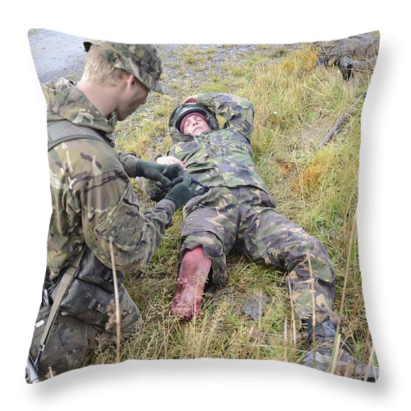 A Patrol Medic Applies First Aid Throw Pillow by Andrew Chittock
