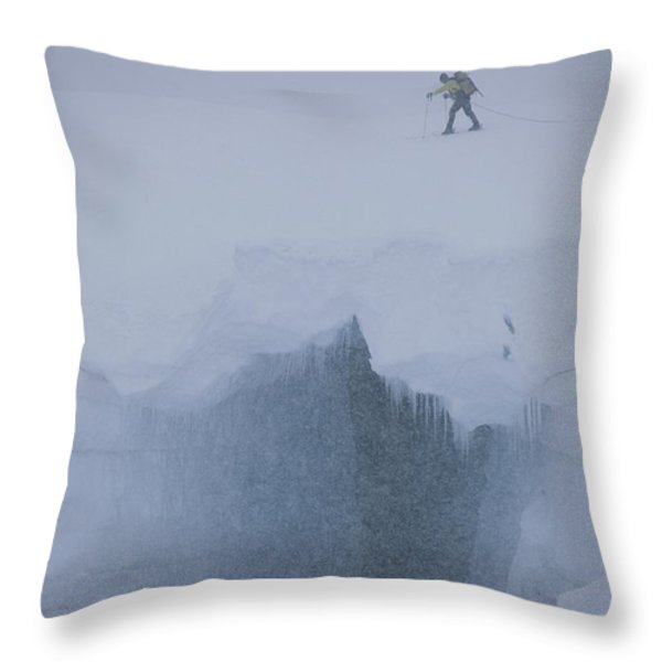 A Skier Above A Deep Glacier Crevasse Throw Pillow by John Burcham