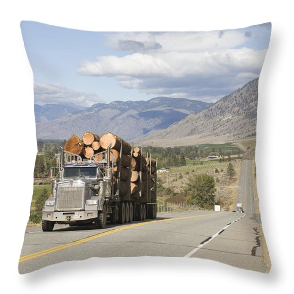 A Truck Carries Logs Down The Highway Throw Pillow by Taylor S. Kennedy