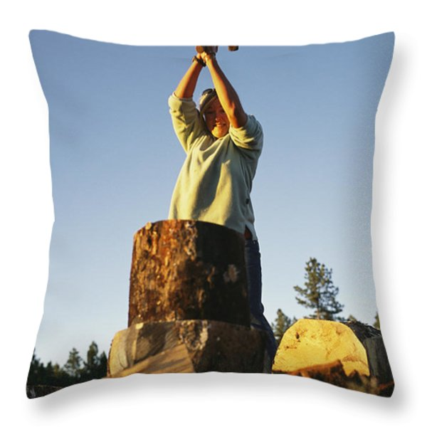 A woman chops wood with Throw Pillow by BOBBY MODEL