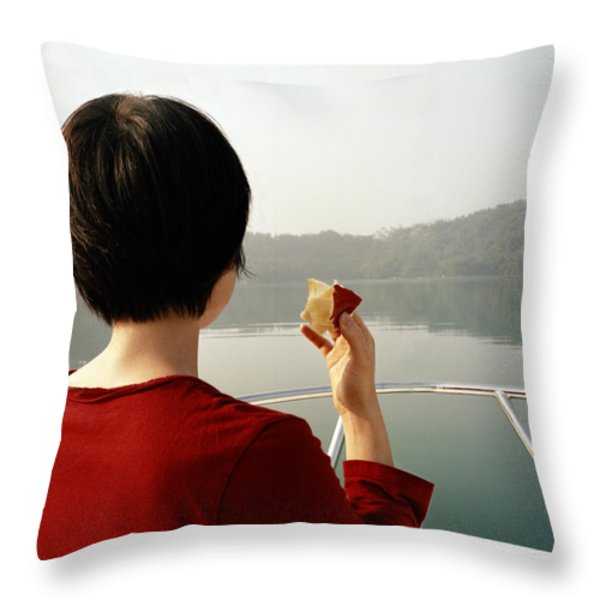 A Woman Eats An Apple While Riding Throw Pillow by Justin Guariglia