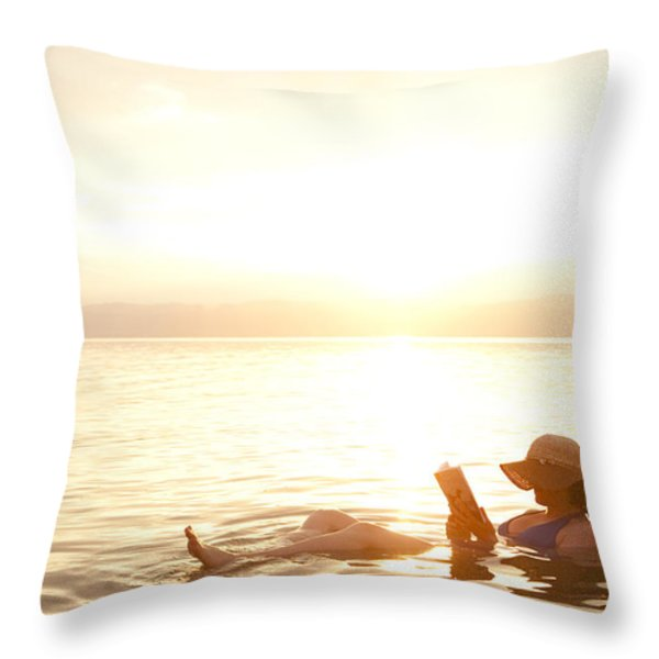 A Woman Reads A Book While Floating Throw Pillow by TAYLOR S. KENNEDY