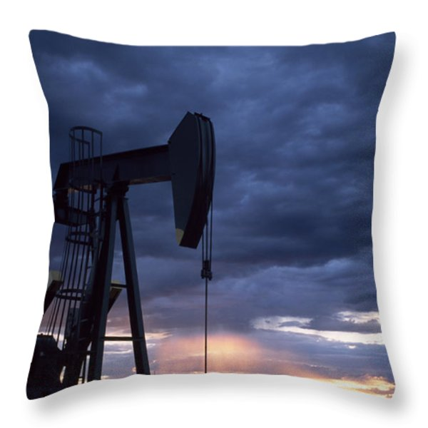 An Oil Rig Silhouetted At Sunset Throw Pillow by Joel Sartore