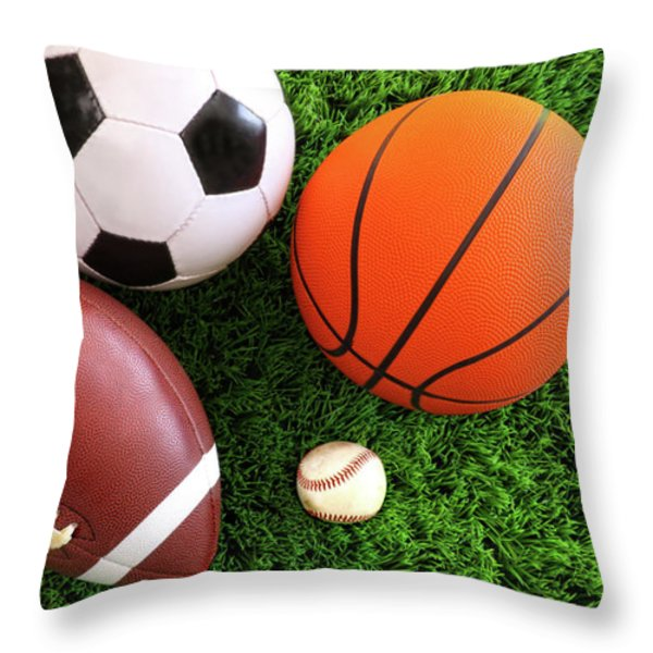 Assortment of sport balls on grass Throw Pillow by Sandra Cunningham