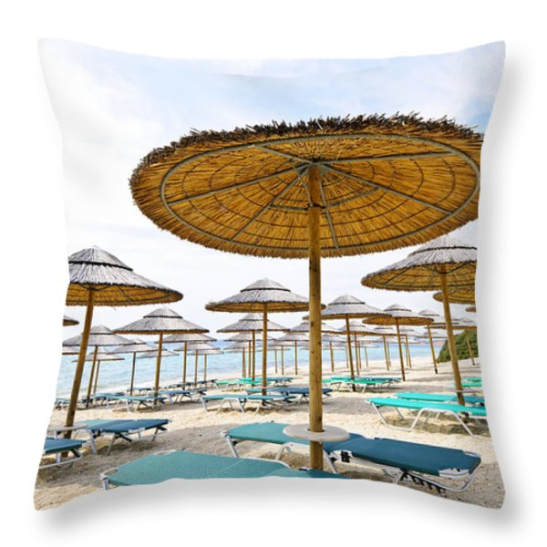 Beach umbrellas and chairs on sandy seashore Throw Pillow by Elena Elisseeva