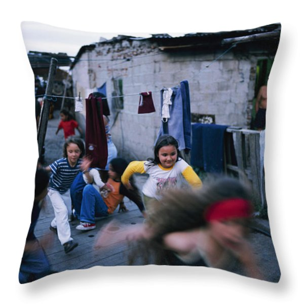 Children Play Around An Abandoned Throw Pillow by Pablo Corral Vega