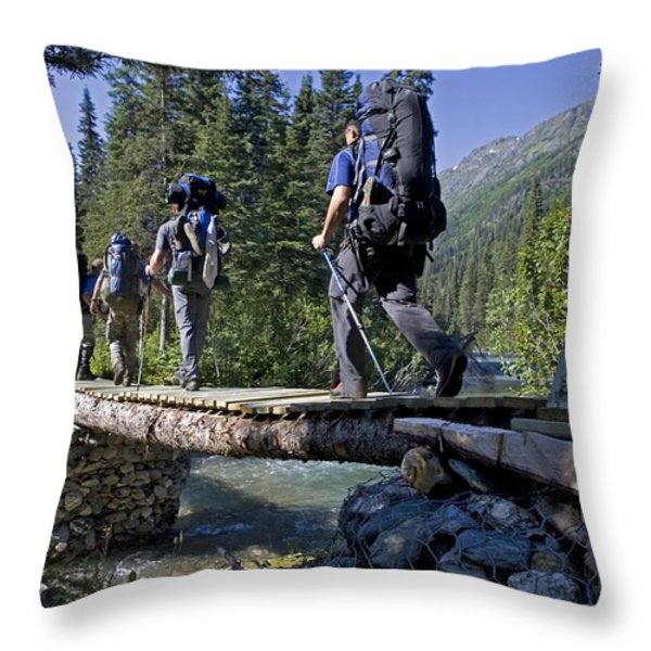 Four Men Cross A River On A Rustic Throw Pillow by Taylor S. Kennedy