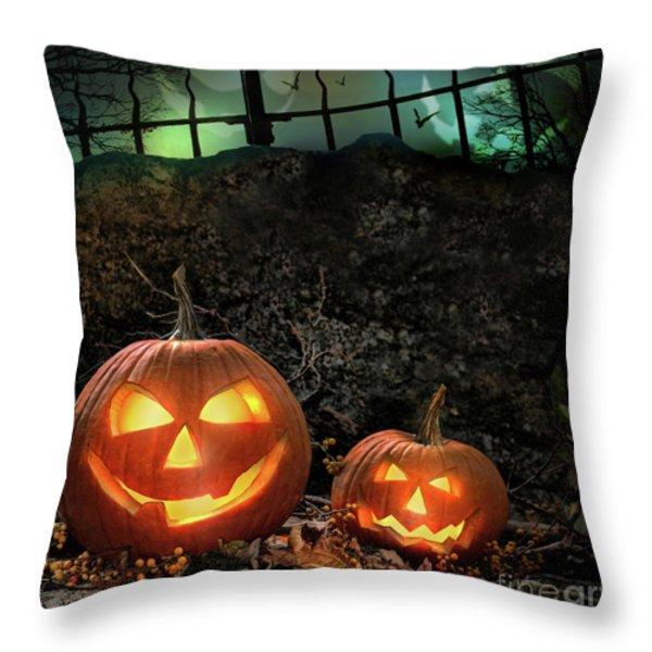 Halloween pumpkins on rocks  at night Throw Pillow by Sandra Cunningham
