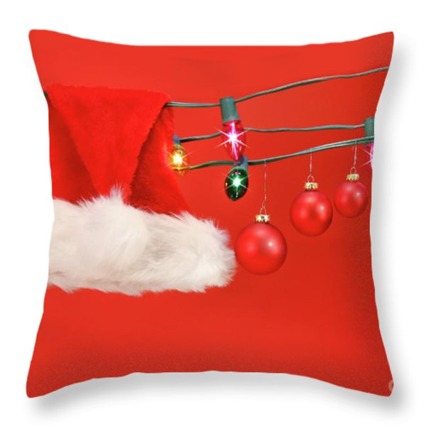 Hanging lights with santa hat Throw Pillow by Sandra Cunningham