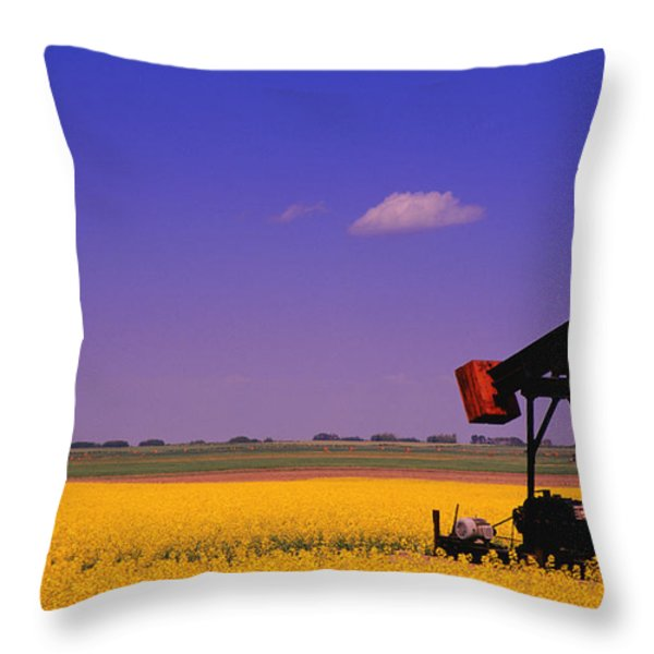 Pumpjack In A Canola Field Throw Pillow by Carson Ganci