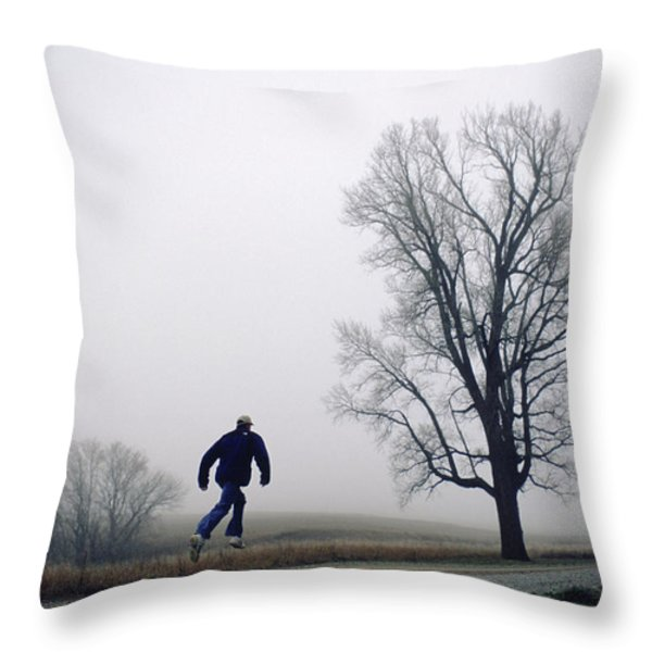 A Man Leaps In The Air On A Gravel Road Throw Pillow by Joel Sartore