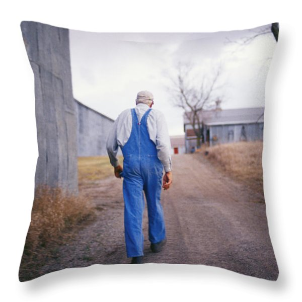 An Elderly Farmer In Overalls Walks Throw Pillow by Joel Sartore