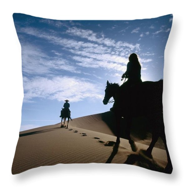 Horseback Riders In Silhouette On Sand Throw Pillow by Axiom Photographic