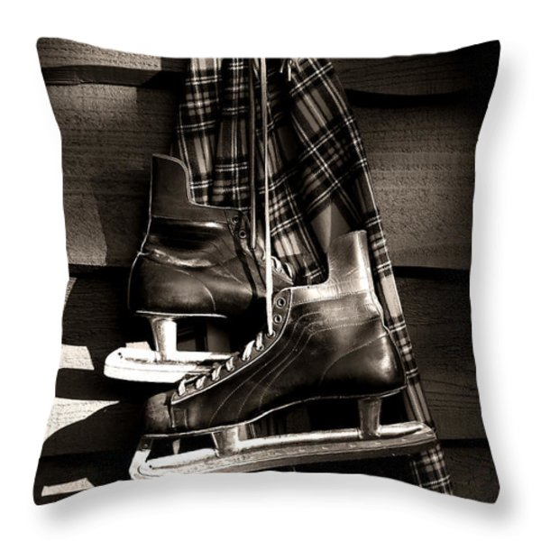 Old hockey skates with scarf hanging on a wall Throw Pillow by Sandra Cunningham