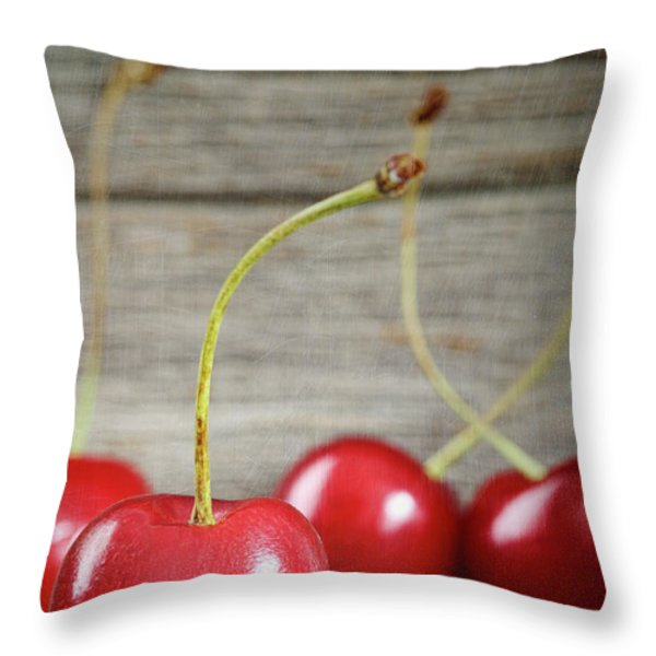 Red cherries on barn wood Throw Pillow by Sandra Cunningham