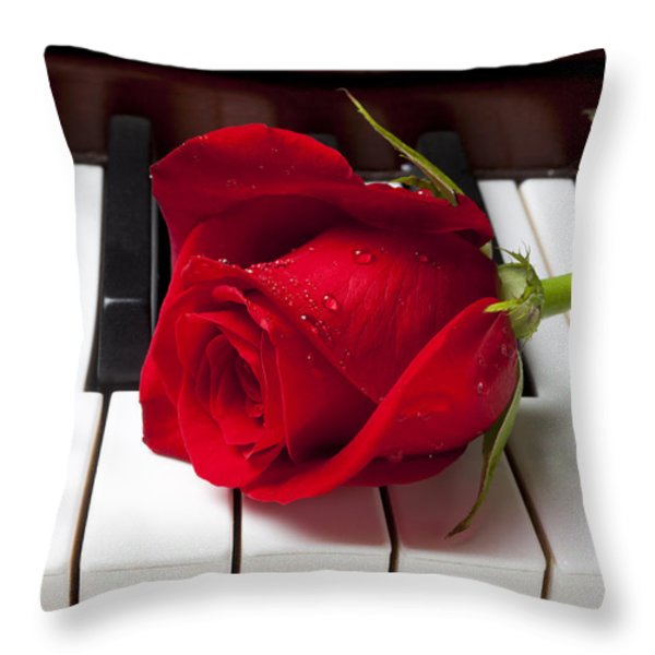 Red rose on piano keys Throw Pillow by Garry Gay