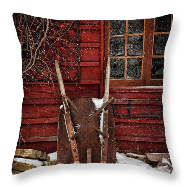 Rusty wheelbarrow leaning against barn in winter Throw Pillow by Sandra Cunningham