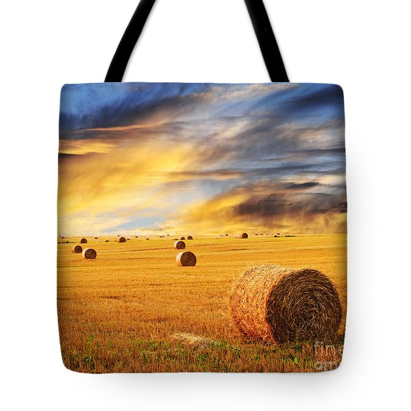 Golden sunset over farm field with hay bales Tote Bag by Elena Elisseeva