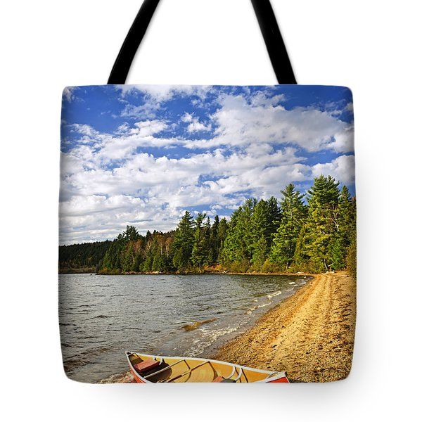 Red Canoe On Lake Shore Tote Bag by Elena Elisseeva