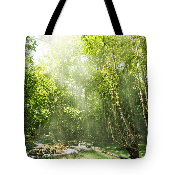 waterfall in rainforest Tote Bag by ATIKETTA SANGASAENG