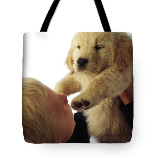Boy Holding Puppy Up Tote Bag by Ron Nickel