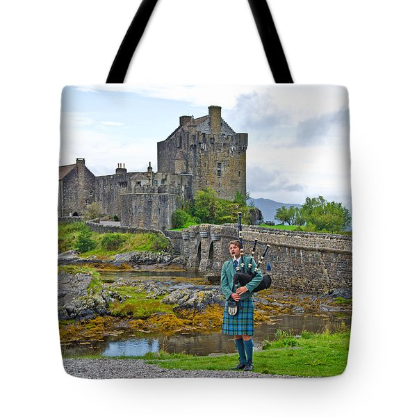 Eilean Donan Castle and the Lone Piper Tote Bag by Chris Thaxter