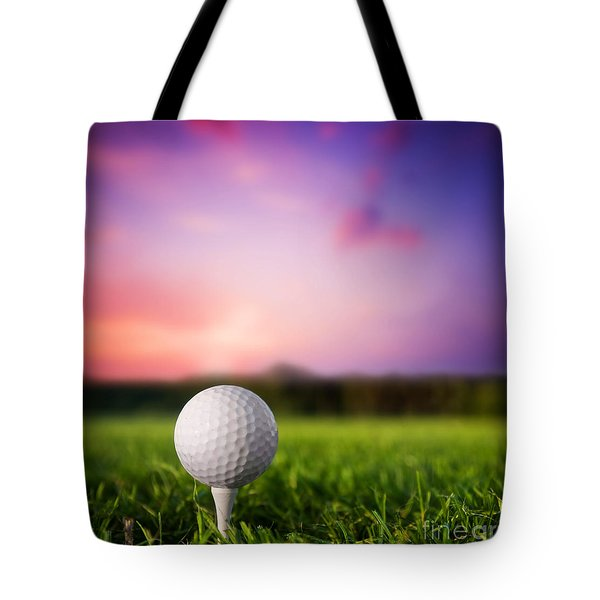 Golf ball on tee at sunset Tote Bag by Michal Bednarek