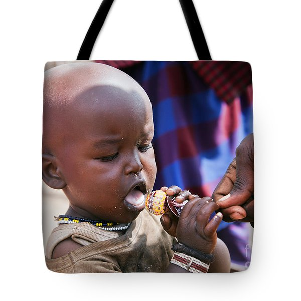 Maasai Child Trying To Eat A Lollipop In Tanzania Tote Bag by Michal Bednarek