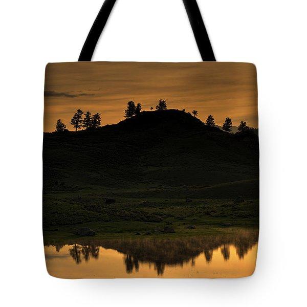 Tote Bag featuring the photograph Sunrise Behind A Yellowstone Ridge by Bill Gabbert