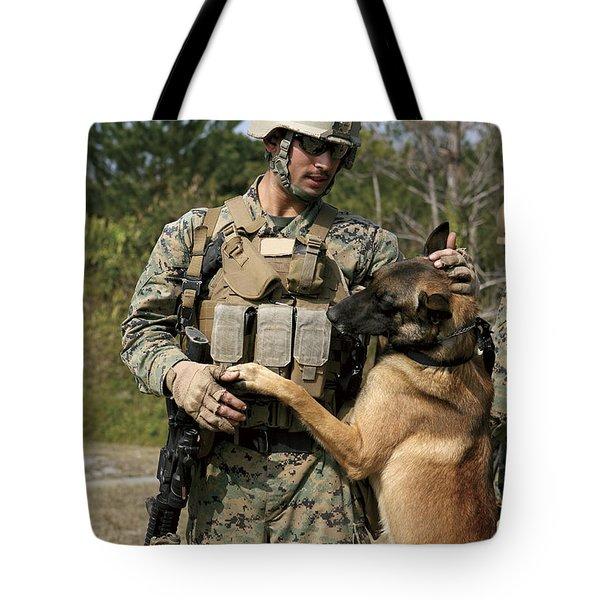 A Dog Handler Gives Positive Tote Bag by Stocktrek Images