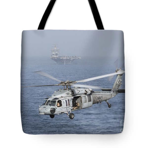 A Mh-60s Knighthawk Conducts A Vertical Tote Bag by Gert Kromhout