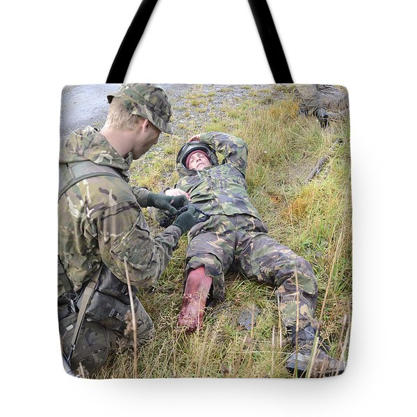 A Patrol Medic Applies First Aid Tote Bag by Andrew Chittock